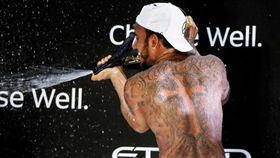 漢彌爾頓在封關站頒獎台上展現身上的刺青。(圖/翻攝自F1官網)
