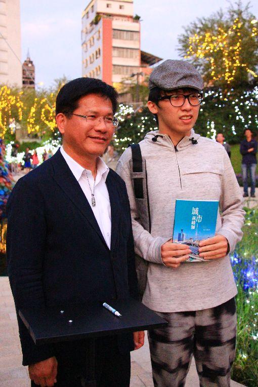 林佳龍柳川辦簽書會 粉絲排隊支持(2)台中市長林佳龍(左)7日下午到柳川直播介紹景點,並舉辦簽書見面活動,就讀台中科技大學的22歲林姓男大生(右)搶到頭香。中央社記者蘇木春攝 107年12月7日
