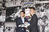 台灣強打王柏融與日本職棒火腿隊簽約,日本火腿球團監督栗山英樹遞上背號99號新球衣以及帽子。(記者林士傑/攝影)