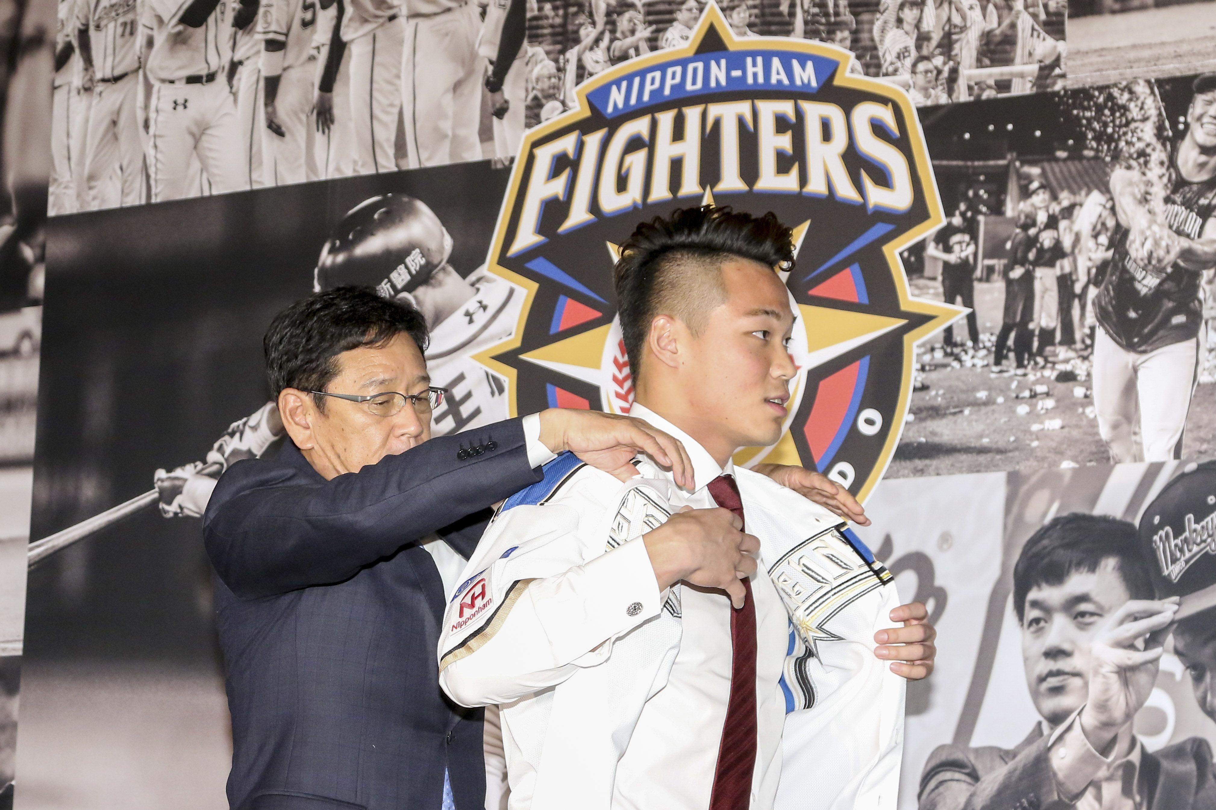 台灣強打王柏融與日本職棒火腿隊簽約,日本火腿球團監督栗山英樹遞上背號99號新球衣以及帽子並為其穿上。(記者林士傑/攝影)