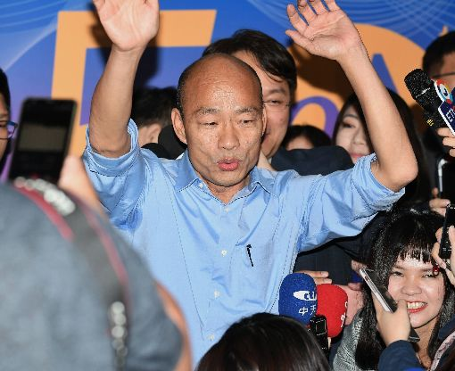 韓國瑜現身政大 揮手致意高雄市長當選人韓國瑜(中)22日晚間赴政大出席政大東亞所50週年慶系列活動,進入會場前,高舉雙手向現場人群揮手致意。中央社記者施宗暉攝 107年12月22日