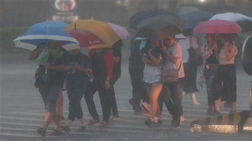 北北基豪雨特報 行人雨中低頭前行對流雲系發展旺盛,由於雨勢加劇,中央氣象局8日下午將北北基等地的大雨特報提升為豪雨特報。台北街頭午後烏雲密布,降下傾盆大雨,行人雨中撐傘低頭前行。中央社記者張新偉攝 107年9月8日