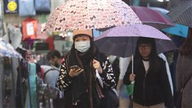 北部東北部濕涼降溫(1)中央氣象局預報,23日東北季風增強且華南雲系東移,北部及東北部氣溫下降,高溫降幅比低溫顯著,高溫僅攝氏22至24度。圖為走在台北街頭的民眾撐傘避雨。中央社記者張新偉攝 107年12月23日