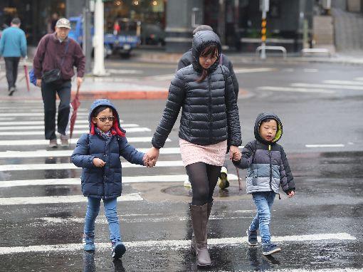 天氣濕冷氣溫低 民眾穿上冬衣禦寒(1)中央氣象局表示,30日清晨各地氣溫仍低,白天起冷空氣強度稍減弱,但因雲多下雨,整體來說氣溫回升幅度不大。民眾穿上厚重的衣服禦寒,穿梭在濕冷的台北街頭。中央社記者徐肇昌攝 107年12月30日