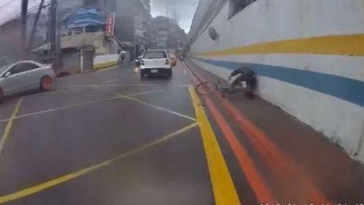 中年男子騎腳踏車行經江北橋時,竟出腳怒踹路旁小黑狗,結果自己摔個狗吃屎(翻攝《爆料公社》)