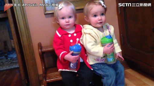▲雙胞胎姊妹擠在一張小小木椅上。(圖/AP/Jukin Media授權)