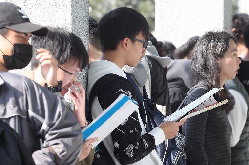 考生認真K書  備戰學測考試(2)大學學科能力測驗25日登場,第一天考英文、國文、社會,考生在試場外認真K書,等待進入考場。中央社記者吳翊寧攝  108年1月25日