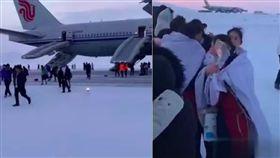 中國國際航空一架波音777客機,周一(4日)在前往洛杉機途中因出現貨艙火警警報,緊急降落俄羅斯阿納德爾機場,冰天雪地中機上人員披著毯子取暖。圖/翻攝自環球網