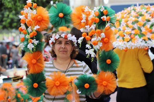 土耳其南部阿達那「國際橙花嘉年華會」據說是土耳其唯一街頭狂歡活動,6日以色彩繽紛踩街遊行進入最高潮。圖為一名攤商製作橙花和柳橙相框供人拍照。中央社記者何宏儒阿達那攝 108年4月7日