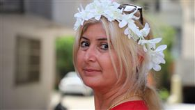 土耳其南部阿達那「國際橙花嘉年華會」據說是土耳其唯一街頭狂歡活動,6日以色彩繽紛踩街遊行進入最高潮。圖為一名婦女頭戴白色橙花頭圈。中央社記者何宏儒阿達那攝 108年4月7日