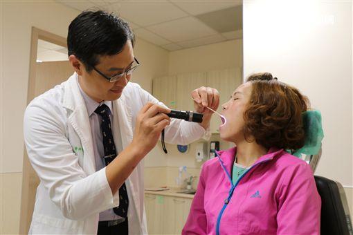 亞大醫院耳鼻喉部主治醫師鄒永恩以棉花棒替患者做味覺檢查。