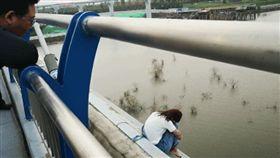 ▲女子抱腿坐在橋邊。(圖/都市快報)