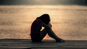 女孩獨自一人坐在海邊哭泣/示意圖/pixabay
