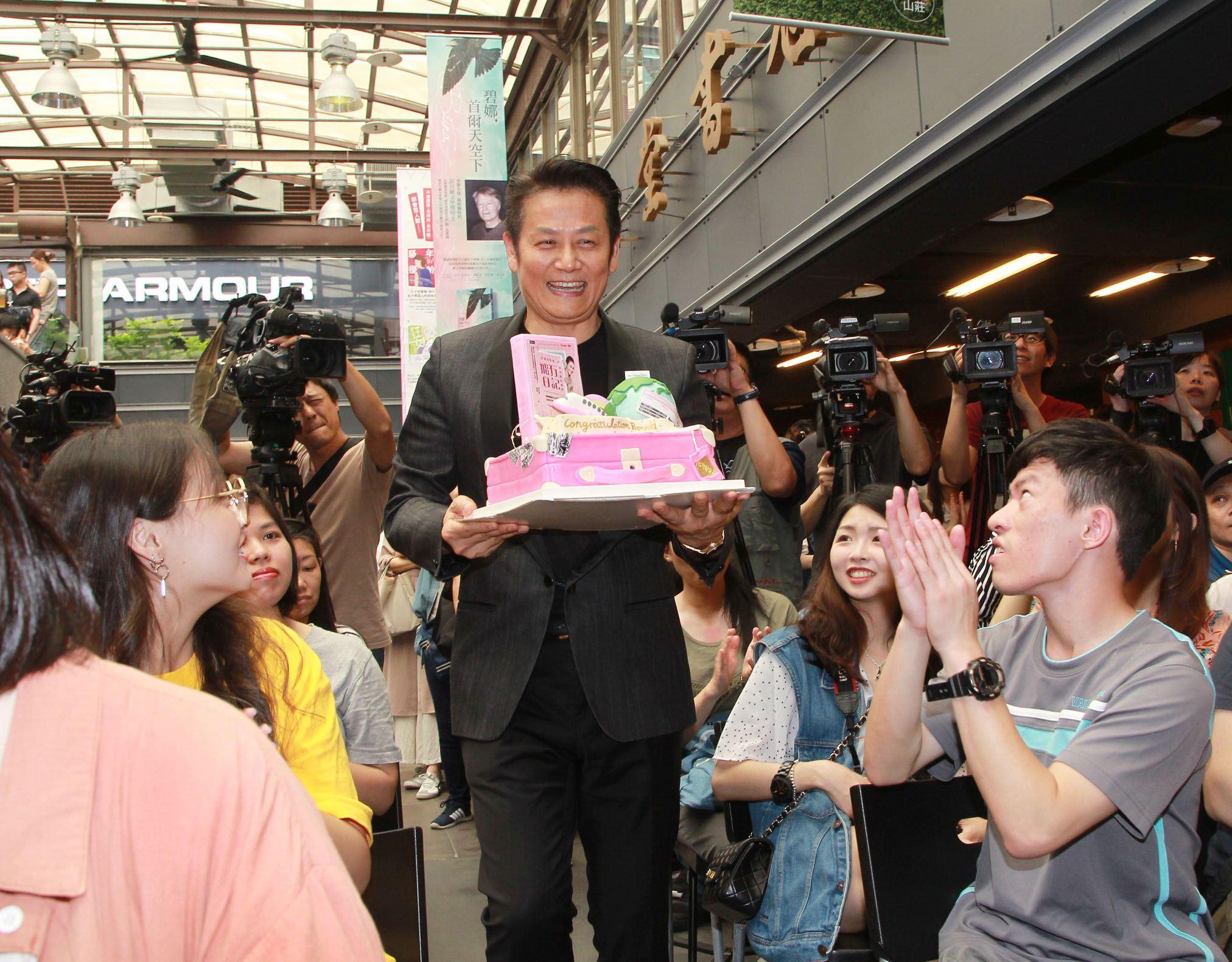 徐乃麟帶著蛋糕為新銳作家阿猷聯空姐邦妮「空服員邦妮從杜拜出發的飛行日記」新書站台。(記者邱榮吉/攝影)