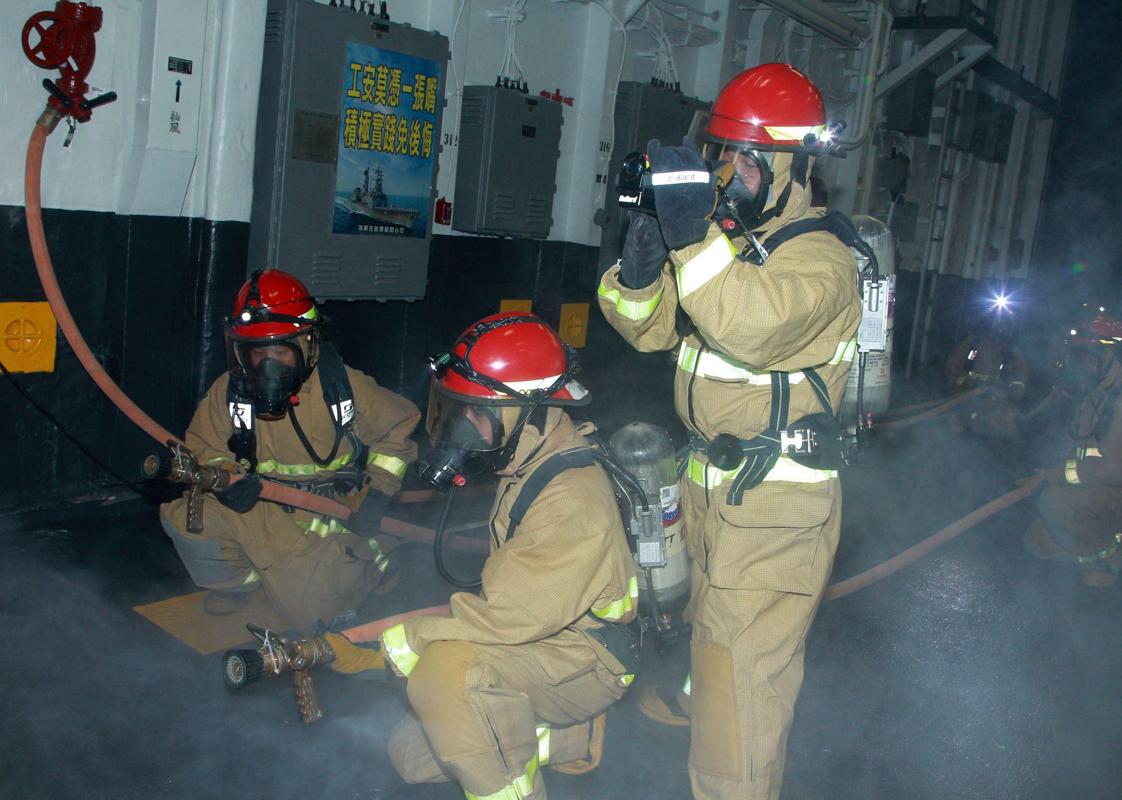 左營艦模擬操敵軍飛彈命中引發大火,修理班著裝前往機庫搶救。(記者邱榮吉/花蓮外海拍攝)