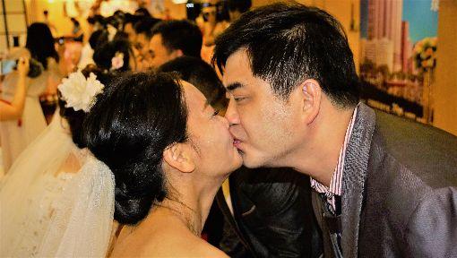24對北京新人情定高雄愛河(1)來自中國大陸北京的24對新人25日來到高雄愛河畔舉辦集團婚禮,攜手定終身,彼此擁吻,現場洋溢甜蜜氛圍。中央社記者程啟峰高雄攝  108年5月25日