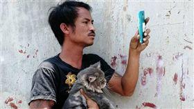 司機逃出時,模樣狼狽,手上還緊抱著他最好的灰貓朋友。(圖/翻攝自กลุ่มคนอาสา กู้ชีพ กู้ภัย Thailand臉書)