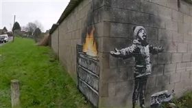 英國威爾斯南部小鎮塔巴特港一處車庫牆上2018年12月出現英國塗鴉大師班克西作品「佳節祝福」,塗鴉出現後,吸引數萬人到場觀賞。(圖/翻攝自班克西IG)
