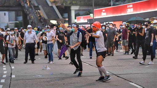 香港反送中 民眾撿催淚彈反擊(2)香港群眾12日上午起占據立法會周邊區域道路,堅定表達「反送中」立場,警方下午陸續投射催淚彈欲驅離人潮,有抗議人士撿起催淚彈反擊,丟向警方所在處。中央社記者王飛華攝  108年6月12日