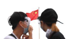 香港反送中 抗議民眾抬頭望見五星旗香港警方12日下午施放催淚瓦斯試圖驅離立法會外反送中的抗議民眾,部分民眾頭戴護目鏡、口罩持續抗爭,有民眾抬頭望著一旁的五星旗。中央社記者王飛華攝 108年6月12日