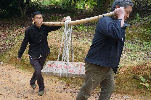 為父立墓碑 烈士之子完成心願烈士王開鎖之子王瑞珍(左)多年來一直希望為父親立碑,最近在台灣有關單位協助下,這個心願得以完成。他和好友一起用扁擔扛著墓碑,前往安放父親骨骸的墓地。中央社記者黃慧敏攝 108年6月22日