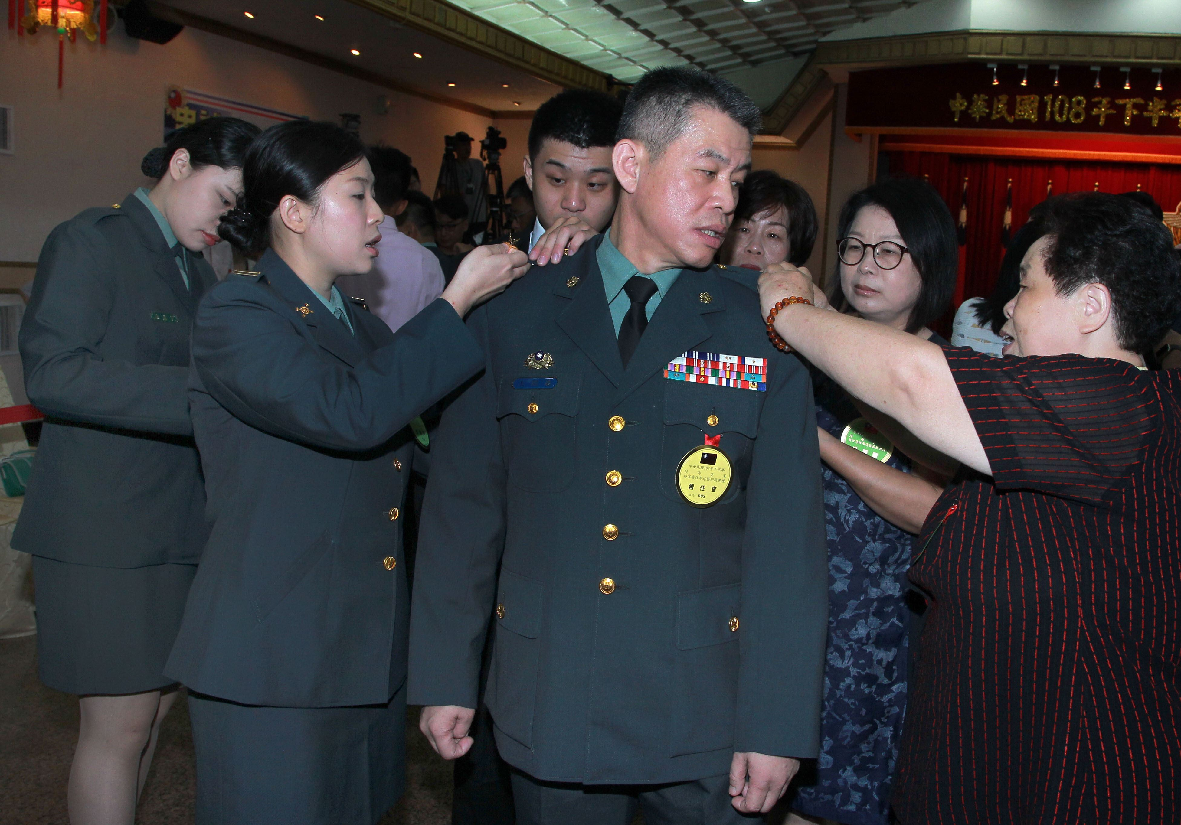 108年下半年陸海空軍將官晉任布達暨授階典禮,晉升中將的王紹華由同樣身為職業軍人的女兒王德霖(左)與家人為其掛上中將階級。(記者邱榮吉/攝影)