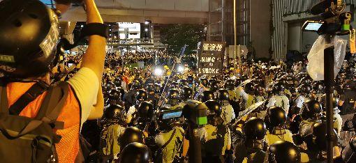 香港太陽花 警方凌晨以催淚彈清場大批香港示威者1日晚間撬開立法會鐵門後進一步占領議場,港警隨即在周邊集結待命,並於2日凌晨零時陸續推進,高舉黑色催淚彈警告牌,宣示進行清場。中央社記者張謙攝 108年7月2日