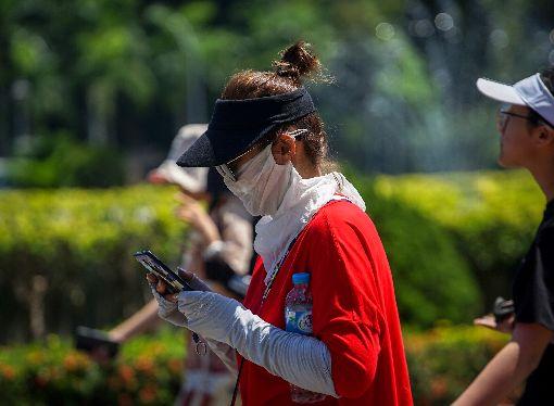高溫炎熱  北市紫外線達危險級(1)中央氣象局表示,16日受熱帶性低氣壓或颱風外圍沉降影響,各地高溫炎熱,台北市區下午紫外線指數達危險級,路上行人戴上口罩、袖套防曬。中央社記者裴禛攝  108年7月16日