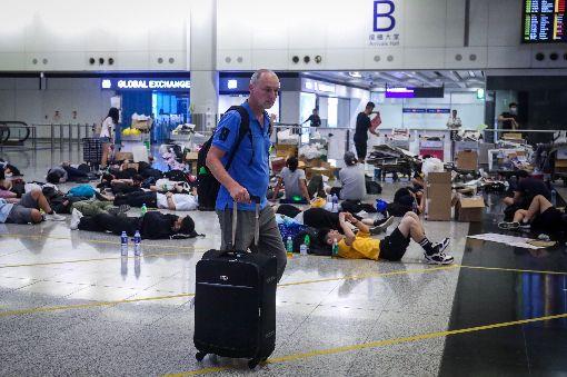 反送中示威者機場過夜(1)香港反送中示威者號召全民罷工、百萬人塞爆機場,造成香港機場12日下午4時起全數航班取消,13日清晨5時示威者剩不到百人,旅客在示威者身處的大廳穿梭。中央社記者吳家昇攝  108年8月13日