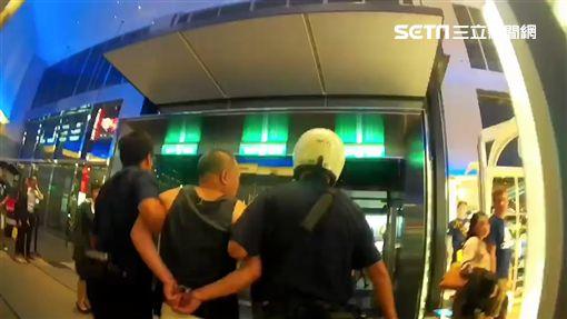 林男砸毀新光三越A11館的蘋果專賣店後,遭到警方雙手反銬帶離現場(翻攝畫面)