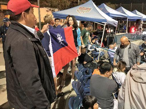 女壘海峽大戰 台灣女婿護國旗遭趕出場中華隊赴美國加州爾灣參加U19世界盃女壘賽,熱情僑胞拿出大面國旗,遭到大會制止。一名美國籍的台灣女婿(右)與大會人員爭執,遭趕出球場。中央社記者林宏翰加州爾灣攝 108年8月17日