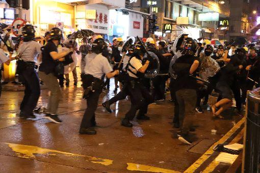 港警被圍毆開槍示警  疑似反送中首度發射實彈(3)香港「反送中」遊行25日晚疑似首度出現警方發射實彈。入夜後,有約10名員警在抗爭現場遭示威者包圍追打,被圍員警拔出隨身的左輪手槍對空鳴槍示警,示威者一哄而散,並遭增援的員警追捕。圖為混戰場景。中央社記者張謙香港攝  108年8月25日