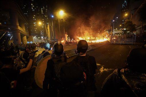 香港反送中運動31日傍晚上演暴力抗爭場面,除警方發射催淚彈、出動水砲車外,示威者也頻丟汽油彈等,雙方對峙至入夜仍持續,灣仔一帶街道燃起熊熊火光。