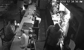 歹徒持槍搶劫!酒吧男輕鬆「滑手機」 遭長槍指竟淡定點菸(圖/翻攝自YouTube)