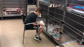 男孩坐籠前唸故事給狗狗聽 每次結束都求媽:可以帶一隻回家嗎 (圖/翻攝自臉書社團Dogspotting Society/Jennifer Baugh)