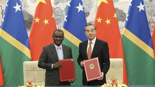 索羅門群島外交部長馬內列(左)21日與中國國務委員兼外交部長王毅(右)在北京簽署建交公報。(中新社提供)