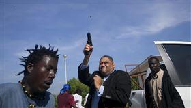 有數名抗議民眾猛拉海地參議員費提耶(Jean Marie Ralph Fethiere)的車門,怒氣沖沖地向他吼叫後,他直接走下車連開好幾槍,嚇得現場民眾驚慌失措,四處竄逃。(圖/美聯社/達志影像)