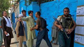 阿富汗28日舉行總統大選投票,但叛亂分子在全國各地投票所發動攻擊,造成至少1人死亡、10多人受傷。圖為維安人員在查拉拉巴一處投票所外執行安檢。(法新社提供)