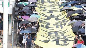 禁蒙面法首日 港人仍戴口罩遊行5日是香港實施禁蒙面法的第一天,但是許多港人仍然戴著口罩遊行抗議。圖為遊行隊伍下午3時許抵達灣仔,龍頭手持「我願榮光歸香港」的布條。中央社記者張謙香港攝 108年10月5日