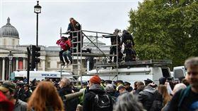 「反抗滅絕」發起全球抗議運動,要求各國政府減少碳排量,展開為期兩週的全球示威活動。圖為7日英國倫敦示威者爬上鐵架遭警方驅離。(圖/中央社/法新社提供)