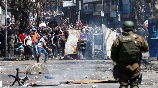 智利政府6日調漲地鐵票價,引發中學和大學生率先發難抗議,後來演變成反政府示威,表達對於總統皮涅拉和軍方的不滿。圖為21日民眾聚集於路障後方,與安全部隊發生衝突。(路透社提供)