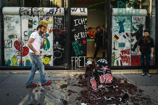 為慶祝柏林圍牆倒塌30週年,法國巧克力雕刻師羅傑(左)9日拿槌子敲毀他用巧克力做成的柏林圍牆復刻版,並把「圍牆」碎片分給路人,讓大家一起品嘗自由。(法新社提供)