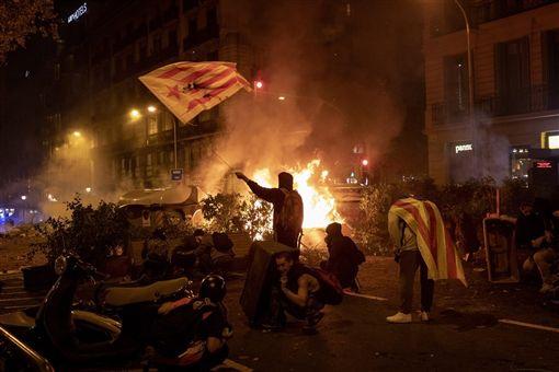 巴塞隆納等加泰隆尼亞城市日前爆發街頭示威,超過600人在示威中受傷。圖為支持加泰隆尼亞獨立的群眾10月18日在巴塞隆納舉辦和平遊行,但越夜越趨暴力,街頭出現火光、煙霧和石塊。(美聯社)
