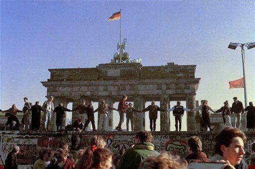 1989年11月9日德國柏林圍牆倒塌,柏林人在柏林牆頂上唱歌跳舞,慶祝東西德邊界開放。(圖/美聯社/達志影像)