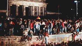 1989年11月9日德國柏林圍牆倒塌,人們在布蘭登堡門前的柏林牆頂上慶祝。(圖/美聯社/達志影像)