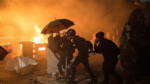 香港中文大學「反送中」學生12日在校園周邊與警方對峙,警方向學生發射催淚彈,學生向警方丟汽油彈。(法新社提供)