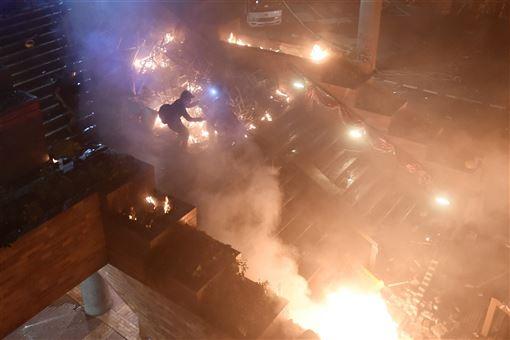 數十名防暴警察凌晨約5時30分從暢運道搶占理工大學大門處,校內示威者向警察丟擲多枚汽油彈並引燃路障,還有人從A座樓層平台丟擲汽油彈,現場一片火海。(法新社提供)