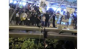 香港理工大學示威者持續被困,上百人18日晚間改用吊繩,試圖跳下馬路逃出校園,似有少數人被前往聲援的電動機車接走。(美聯社)