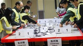 區議會選舉 深夜點票香港近日抗爭情勢逐漸趨緩,24日區議會選舉如期舉行,晚間10時30分結束投票後進行點票作業,灣仔一家投票站工作人員25日凌晨仔細清點選票。中央社記者吳家昇攝 108年11月25日