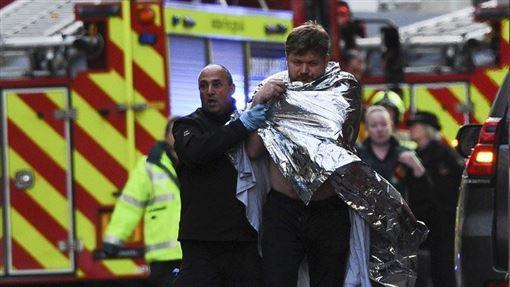 英國倫敦29日發生恐怖攻擊事件已知3死數傷,其中嫌犯遭警方擊斃,2名受到攻擊的平民不幸傷重身亡。圖為警方協助傷者就醫治療。(法新社提供)